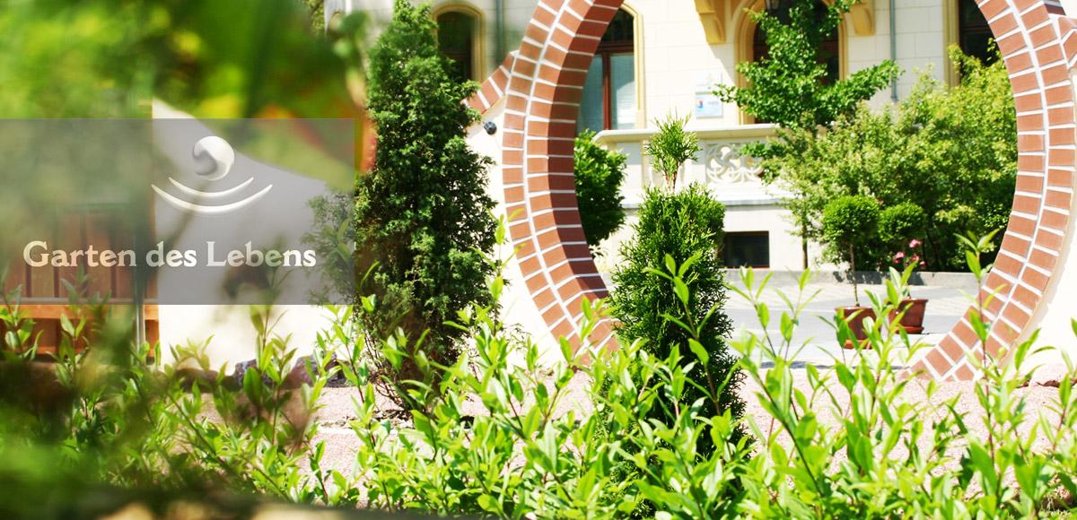Ansicht eines Ausschnittes Garten des Lebens mit Logo, im Hintergrund Klinik im Leben in Greiz